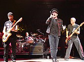 Four men on a stage, all wearing black clothing. Two are playing guitars, one is sitting behind a drum set, and one is holding a microphone up to his mouth. In the background is a crowd of people.