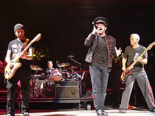 U2 performing on a concert stage. The Edge and Adam Clayton, playing guitars, flank Bono in the foreground, while Larry Mullen, Jr. is behind a drum kit in the background.