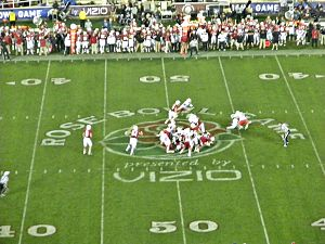 Several American football players in red and white uniforms in action at the mid-field area of the stadium with a large logo visible on the field.