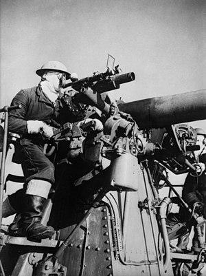 Direct fire - A gunner aiming a QF 4 inch Mk V naval gun for direct firing