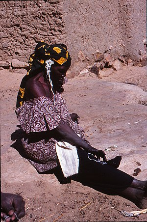 Tie-dye - A jau woman from the dyers' caste prepares a cotton band for tie-dye colouring, Sangha, Mali, 1980.