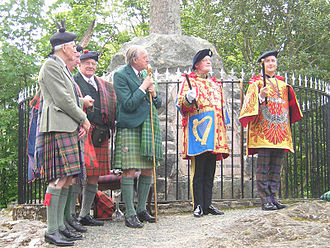 Private Officer of Arms - The Honourable Adam Bruce (far right) at his installation as Finlaggan Pursuivant of Arms of Clan Donald. Finlaggan wears a tabard emblazoned with the arms of his employer, the Chief of Clan Donald.