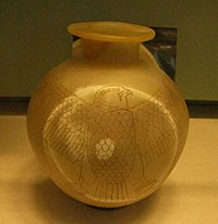 A yellow spherical jar inscribed with a falcon wrapping around the circumference.