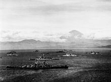 Black and white photo depicting 13 World War II-era warships anchored close together near the coast of a body of water. Steep mountains are visible in the background.