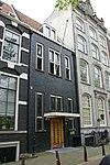 foto van Dubbel huis met gevel, versierd met grote boogblokken en voorzien van een trappentop in het midden