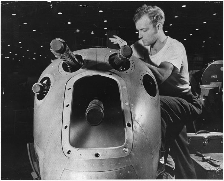 Ofbyld:An armorer's assistant in a large western aircraft plant works on the installation of one of the machine guns in the... - NARA - 196367.jpg