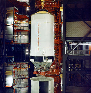 S-II - The S-II stage during stacking operations of Apollo 6 in the VAB. Ordinarily the interstage (striped structure immediately below the stage) would be attached to the S-II first. The flight stage was delayed, resulting in the interstage being attached to the S-IC instead.