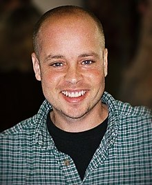 A portrait photograph of a Caucasoid man; he's wearing a checkered shirt while looking into the camera and smiling.