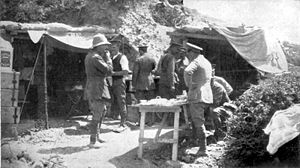 Two dugouts with tents for awnings. Wooden boxes are stacked nearby. Men in uniforms with peaked caps (and one with a solar topee) stand around a wooden folding camp table.