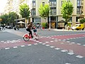Bikeshare rider crosses intersection of two bikeways (18603243199).jpg