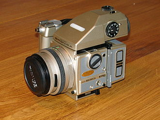 Bronica - ETRSi 40th anniversary edition in champaign metallic colour, with manual shutter-release handgrip and metered prism viewfinder attached, released 9 May 1999
