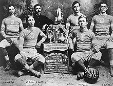 "A black-and-white image of young male basketball players dressed in team uniform, sitting around a display that holds trophies. The plaque below the display reads ""Pan-American Basket Ball Champions."""