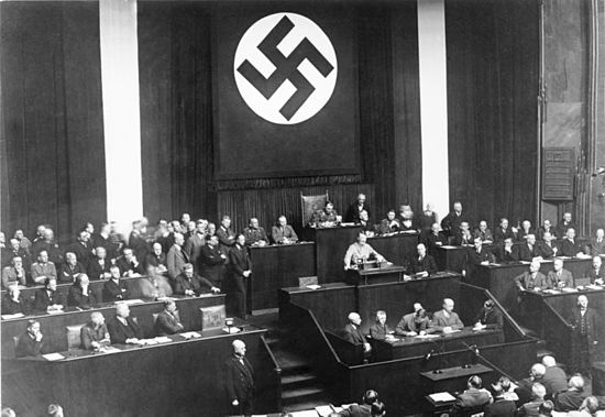 Adolf Hitler addressing the Reichstag on 23 March 1933. Seeking assent to the Enabling Act, Hitler offered the possibility of friendly co-operation, promising not to threaten the Reichstag, the President, the States or the Churches if granted the emergency powers. Bundesarchiv Bild 102-14439, Rede Adolf Hitlers zum Ermachtigungsgesetz.jpg