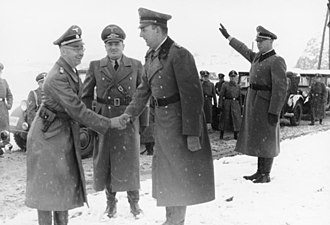 Kurt Daluege - Daluege (right) in Cracow in 1939, shaking hands with Heinrich Himmler (left).  Hans Frank (center) is also standing between the two men.