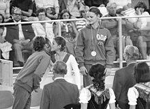 One girl in a track suit with a medal around her neck looks on as two girls congratulate each other
