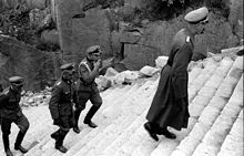 Four men dressed in SS uniforms climb the stone-cut stairs of death, one of them is smoking a cigarette.