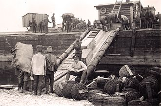 Canadian Siberian Expeditionary Force - A Canadian gunner (seated) supervises the loading of a barge by prisoners.