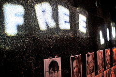 Row of portraits, and lights spelling out the words 'FREE LIU'