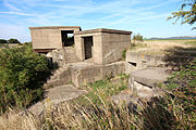 View of a partly overgrown concrete structure built on two levels, with two small concrete cabins above a concreted pit in which several alcoves are visible
