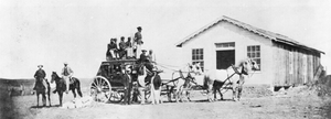 Central Overland California and Pikes Peak Express Company - Typical stagecoach of the Concord type used by express companies on the overland trails. Soldiers guard from atop, ca. 1869
