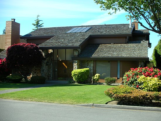 A 1970s-built home with cedar panelling and a front yard with a large section of lawn and a tall-tree border in Richmond, British Columbia.