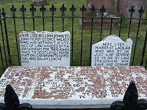 "Wigtown - Covenanters' graves. The recumbent stone in the foreground is the grave of Margaret Willson, and, behind it, the upright stone on the right is that of ""Margrat Lachlane"" (Margaret McLaughlin), these being the two women who were executed by drowning (according to tradition, this took place at the location of the present-day Martyr's Stake). The upright stone on the left is that of the three Covenanter men who were hanged at the same time."
