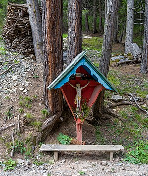 Wayside cross and stack of firewood in the forest of Bulain Gröden