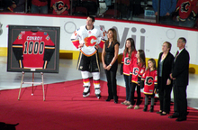 a man is pictured alongside his wife and three daughters as he is presented with a framed hockey jersey with the numeber 1000 on its back.