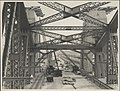Cranes and workmen on the central roadway of the Sydney Harbour Bridge, 1932 (8282717653).jpg
