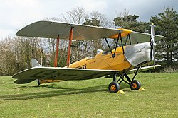 A biplane in yellow and silver livery stands parked in the middle of a field.