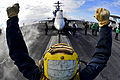 Defense.gov News Photo 110201-N-6003P-225 - An aircraft director guides an F A-18C Hornet onto a catapult aboard the aircraft carrier USS Harry S. Truman CVN 75 in the Atlantic Ocean on Feb.jpg