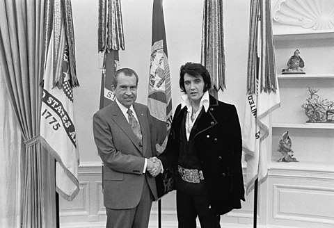 A mutton-chopped Presley, bustin a long-ass velour jacket n' a giant buckle like dat of a funky-ass boxin championshizzle belt, shakes handz wit a funky-ass baldin playa bustin a suit n' tie. They is facin camera n' smiling. Five flags hang from polez directly behind dem wild-ass muthafuckas.