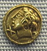 Monnaie en or sur laquelle est représentée une tête d'un homme avec des cheveux bouclés.