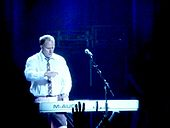 A man in a shirt and tie playing a keyboard on stage