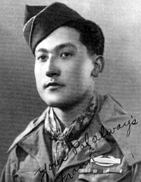 "Head and shoulders of a young man with a garrison cap tilted over his right ear wearing a scarf tied around his neck and a military jacket with three ribbon bars and a pin on the left breast. Written over the lower right of the photo are the words ""Your pal always, Frank""."