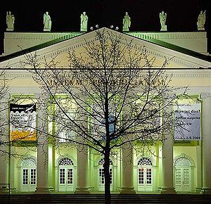 ドクメンタ7で行われた『Stadtverwaldung』(都市緑化、7,000本の樫の木プロジェクト)の20年後の姿。ドクメンタ会場前の大きく育った樫の木の写真