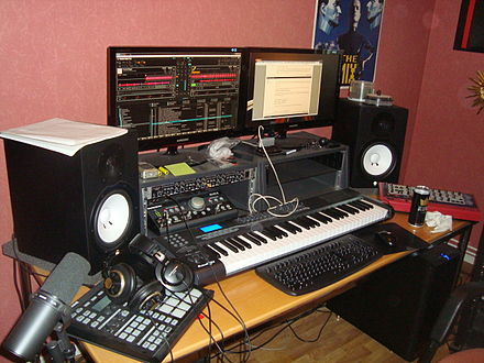 A typical home studio setup for EDM production with computer, audio interface and various MIDI instruments. Friend's home studio (by David J).jpg