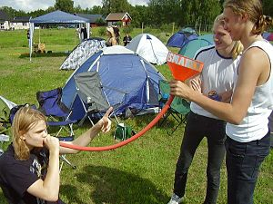 A person sitting on grass outside holds an orange pipe to their mouth while two people standing next to them hold the other end of the pipe with a funnel attached.