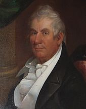A man with gray hair and a ruddy complexion wearing a black jacket and frilly white vest