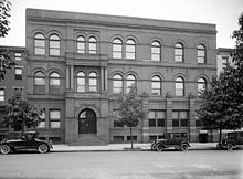 A rectangular, Victorian-style brick building with several trees and three cars from circa 1920 in front.