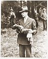 German man holding exhumed baby from a mass grave outside the town of Suttrop.jpg