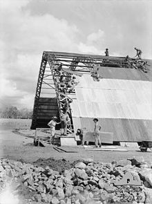 Workmen in slouch hats lay corrugated iron on a large semi-cylinder shaped structure with a metal frame.