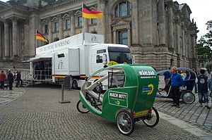 German federal election, 2005 - A bicycle-taxi (velotaxi) in front of the German Reichstag building in Berlin with the Greens livery