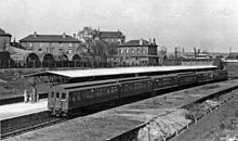 A black-and-white photograph showing a 6-car train at a station. There are detail differences in the carriages, the leading car, unlike the others, has its clerestory extended to the car end and the 3rd and 5th carriage sides are flared at the bottom.