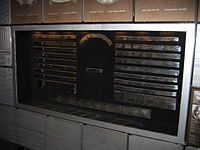 A wall displaying a series of metallic rings which have inscriptions on them