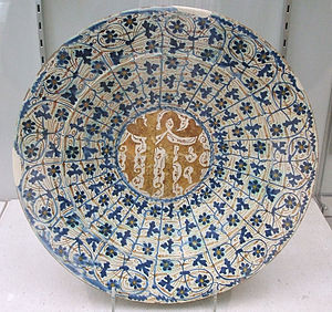 "Tin-glazed pottery - A Hispano-Moresque dish, approx 32cm diameter, with Christian monogram ""IHS"", decorated in cobalt blue and gold luster.  Valencia, c. 1430–1500.  Burrell Collection"