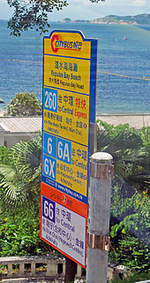 A sign, seen through a vehicle, with large numbers and text in Chinese and English. The upper portion is yellow; a small section at the bottom is in orange