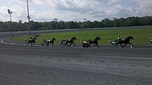 There are six horses racing at Rosecroft Raceway during a qualifying race.