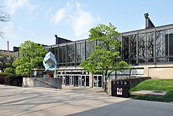a low steel and glass building and concrete courtyard, with the words Paul V. Galvin Library about a bank of doors, flanked by trees and an abstract steel sculpture