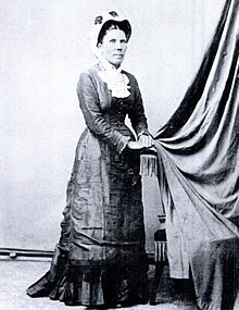 A woman standing in 1890s dress